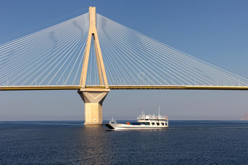 View of a modern bridge and a floating ferryboat. View on Rion-Antirion bridge - the longest cable-stayed bridge in the world and the floating ferryboat beside stock photos