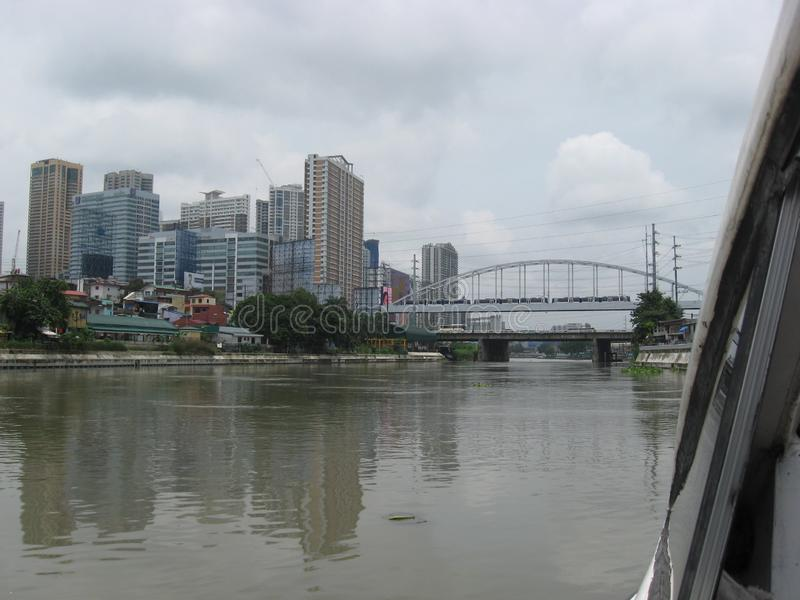 View of modern buildings and the Mandaluyong Boni and Guadalupe bridges along the Pasig river, Manila, Philippines. A view from a ferry boat, of buildings and stock photo