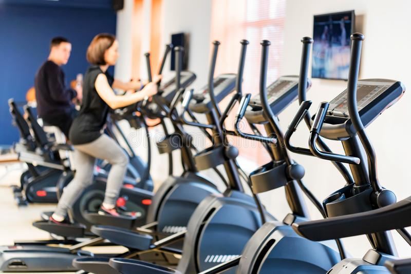 People train on elliptical cross trainers in fitness room stock photo