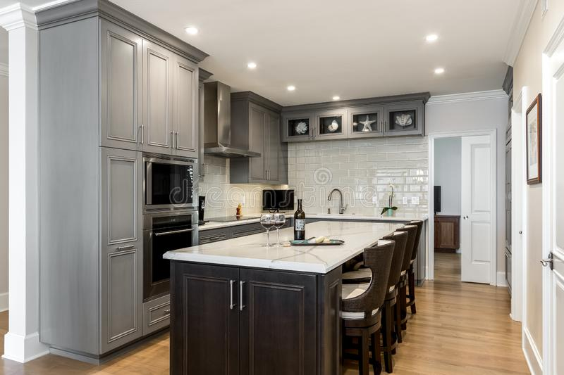 View into modern kitchen remodel with gray cabinets, island, wine and cheese. On counter top stock photography
