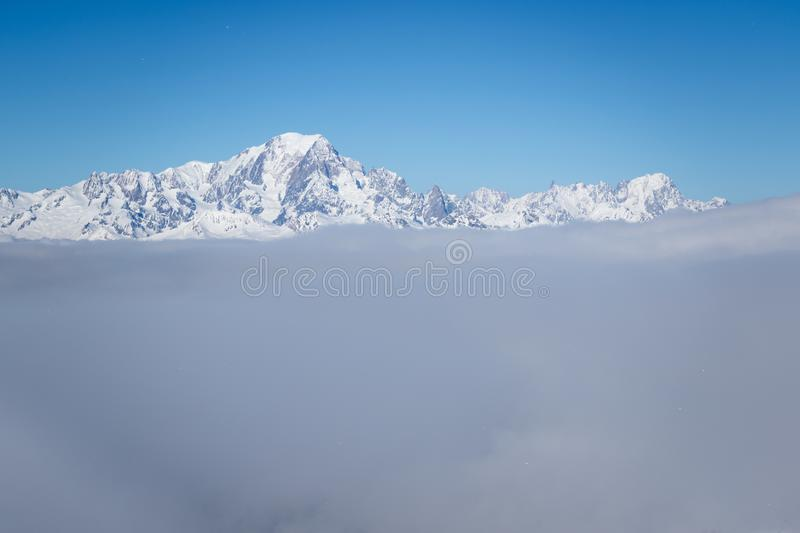 View of Mont Blanc mountain above clouds from Roche de Mio station in La Plagne, French Savoy Alps. Winter scenic scenery, blue stock photos