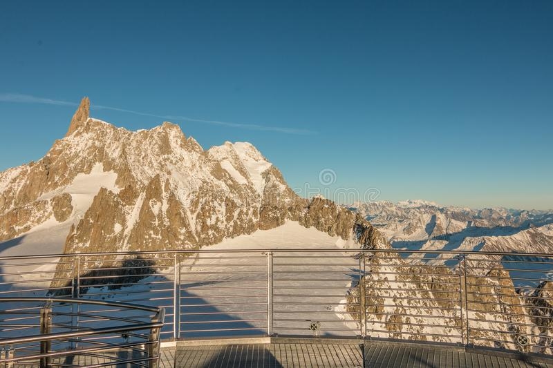 A view from the Mont Blanc top toward the Tooth of the Giant mountain peak at sunset. View from the top of Skyway cable car from Courmayeur ski resort of the stock photos