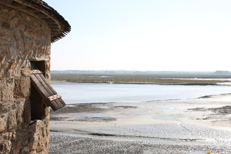 A view from Mont St. Michel over the estuary. Normandy, France. Turret and wooden window in the foreground royalty free stock photo