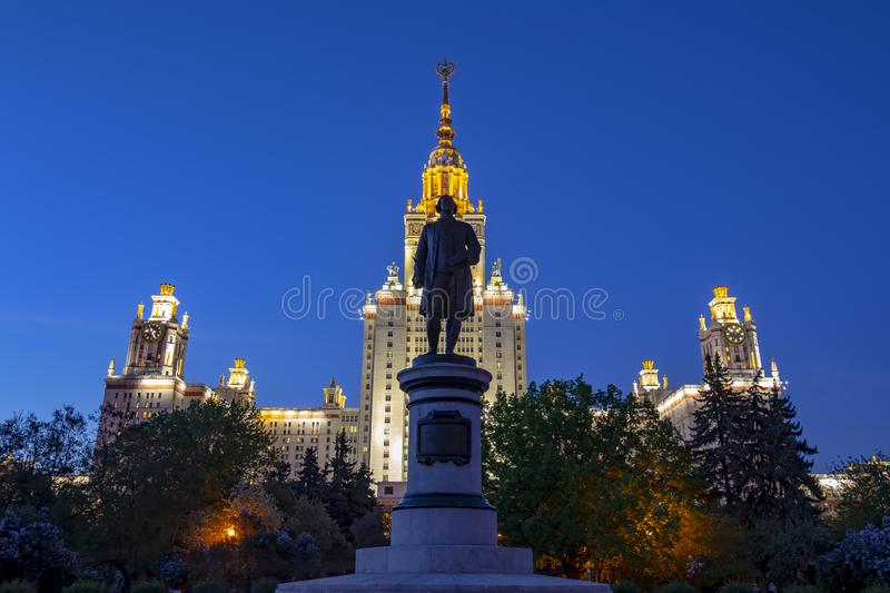 View of the monument to Mikhail Vasilyevich Lomonosov from the side of the main building of Moscow State University. MSU on Sparrow Hills at night, Russia royalty free stock image