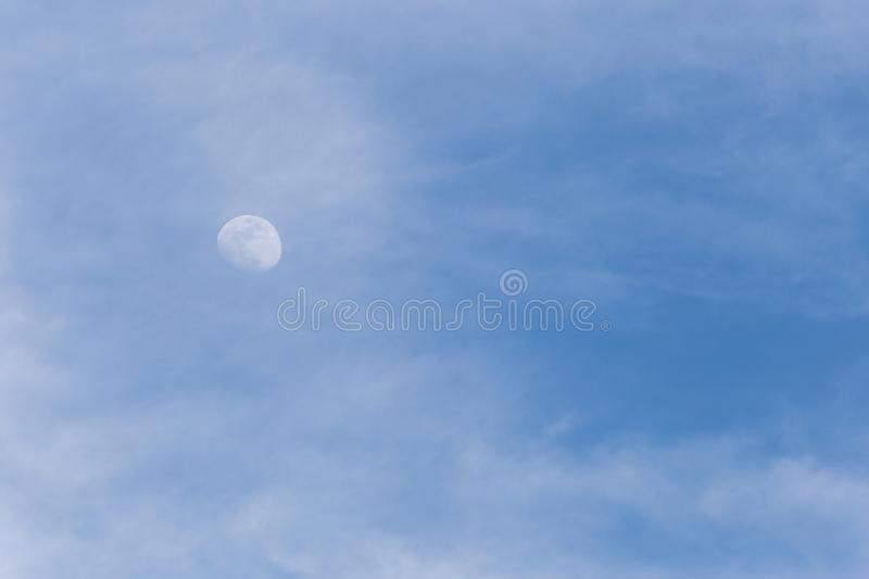 View of moon through some clouds in the blue sky stock image