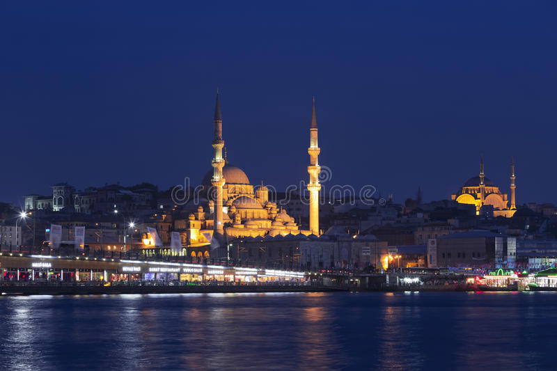 View of the mosque of Istanbul and the Galata bridge. Across the Golden horn at night, Istanbul, Turkey royalty free stock photo