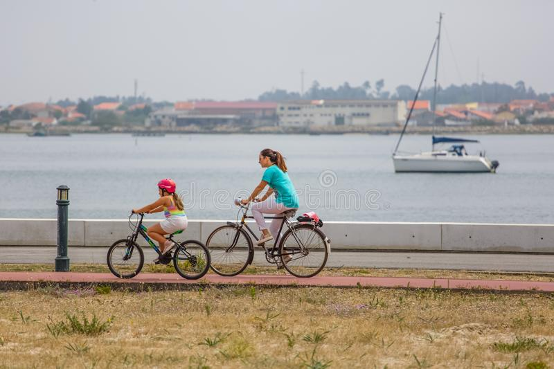 View of a mother and daughter riding a bicycle on a bike path by the river with boat stock photos