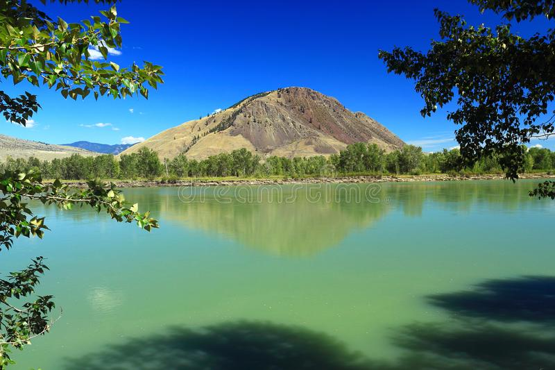 Wide North Thompson River and Mount Paul at Kamloops, BC, Canada. View of Mount Paul on the eastern side of the wide North Thompson River, lined with Cottonwoods royalty free stock photography