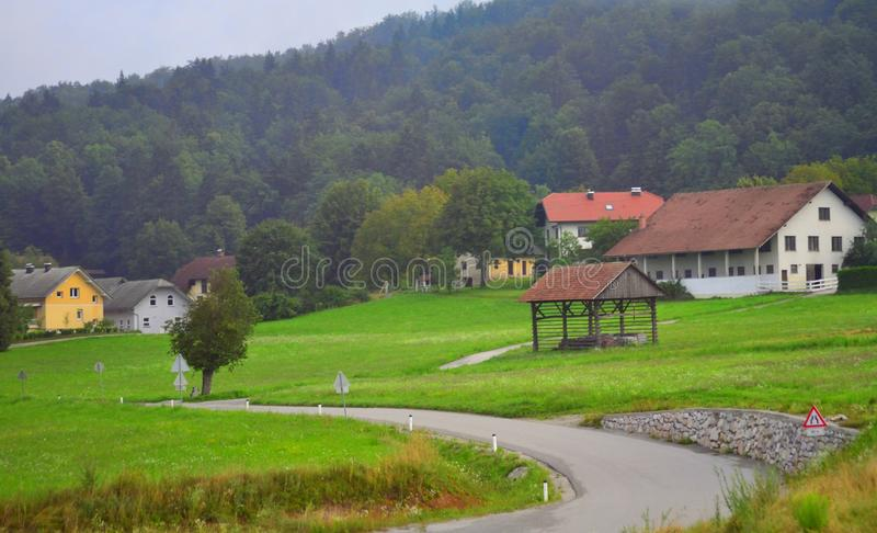 Small mountain village scenery Slovenia Europe. View of mountain houses in the Municipality of Grosuplje seen from A2 motorway on a misty july morning.is a royalty free stock image