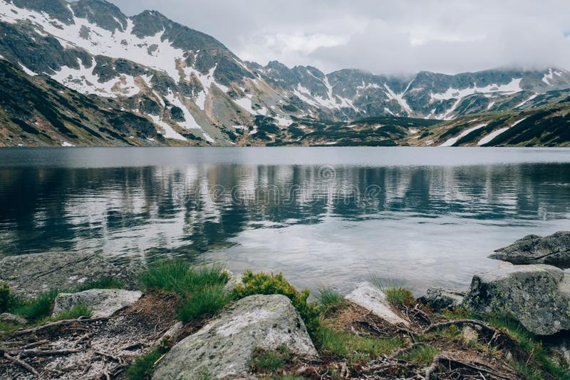 View of a mountain lake in a cloudy day, Valley of Five Lakes Tatra National Park, Poland Dolina Pieciu Stawow Polskich stock image