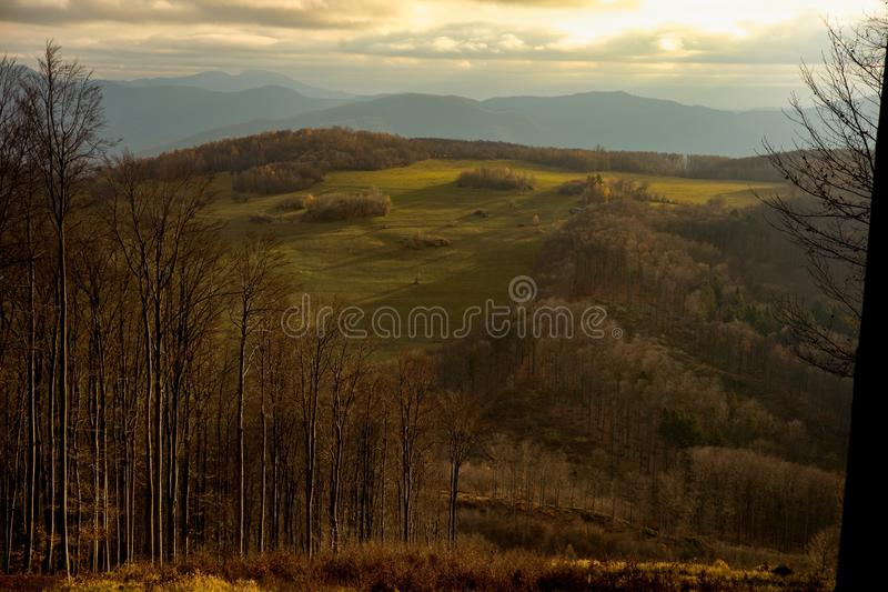 View on the mountain meadows on the hill, Slovakia. Sun is shinning through the clouds which covered blue sky. Meadows are green with some fields and farms. It stock images