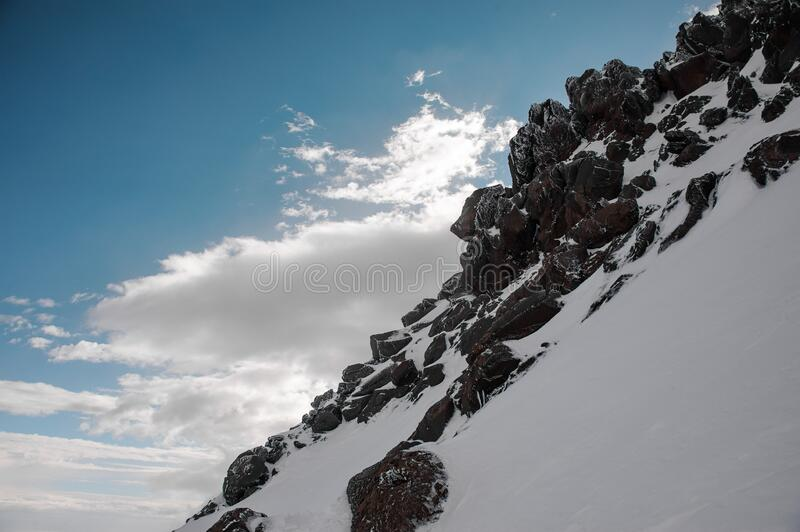 View on the mountain slope covered by snow and black rocks under the blue sky with white clouds. View on the mountain slope covered by snow and black rocks under stock photography