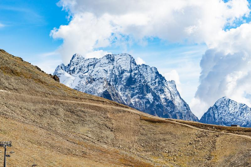 View of mountain slope and snow-covered peak. Travel to North Caucasus region region - view of mountain slope and snow-covered peak from upper ski station of royalty free stock photo