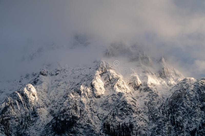 Sunlight breaking trough the clouds in the German Alps. View on a mountain in the snowy German alps, where the sunlight breaks trough a cloud stock photography