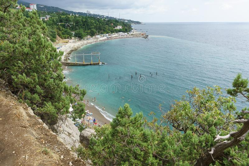 View from the mountain to a small beach near the rock Diva in the resort black sea village Simeiz. Cloudy summer day royalty free stock photos