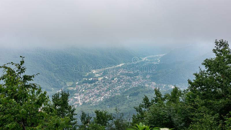 View from mountain valley covered with mist. Krasnaya Polyana, Sochi, Russia royalty free stock photo