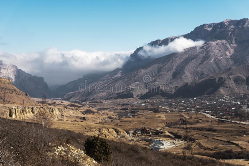 A view of the mountain village in the gorge in the Caucasus. Gray peaks of mountains with clouds and gorges with houses royalty free stock photography