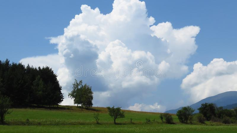 View of mountains landscape and overcast sky. Mountains view. Meadow, trees and blue mountains silhouette on the horizon. Storm clouds coming in over the royalty free stock image