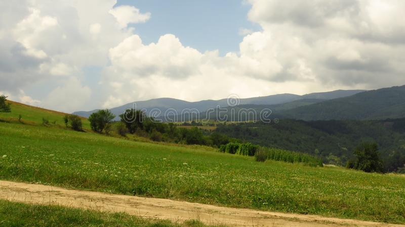 View of mountains landscape and overcast sky. Mountains view. Meadow, trees and blue mountains silhouette on the horizon. Storm clouds coming in over the stock image