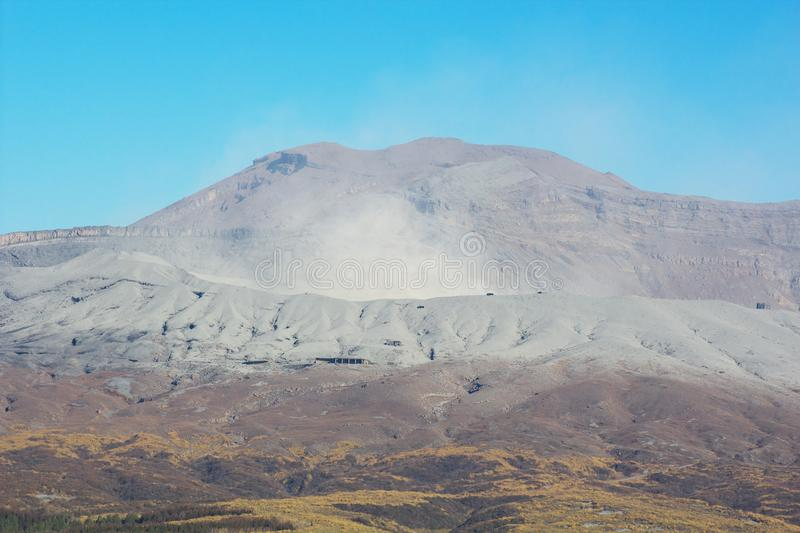 View of Mt. Aso which is spewing smoke at Autumn. An image of nature stock photography