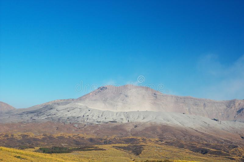 View of Mt. Aso which is spewing smoke at Autumn. An image of nature stock images