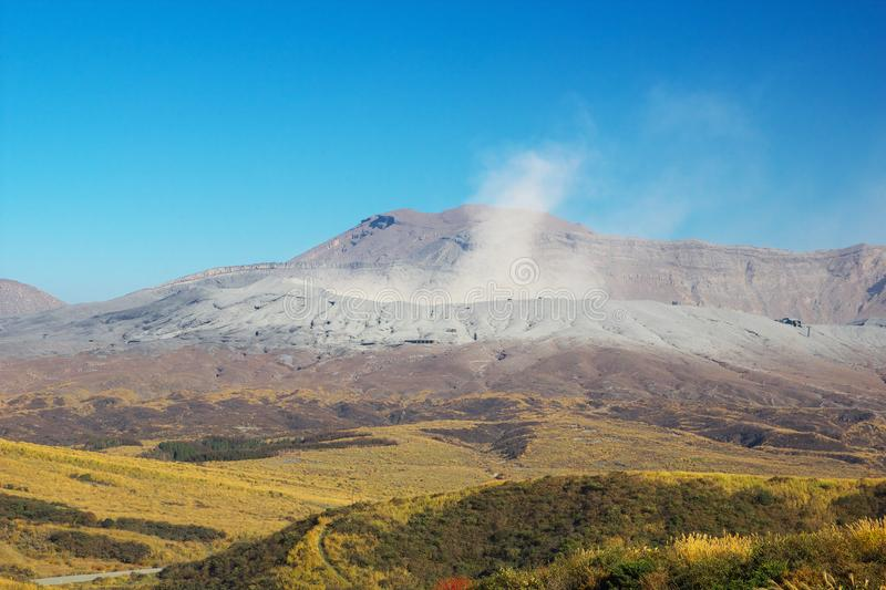 View of Mt. Aso which is spewing smoke at Autumn. An image of nature stock photos