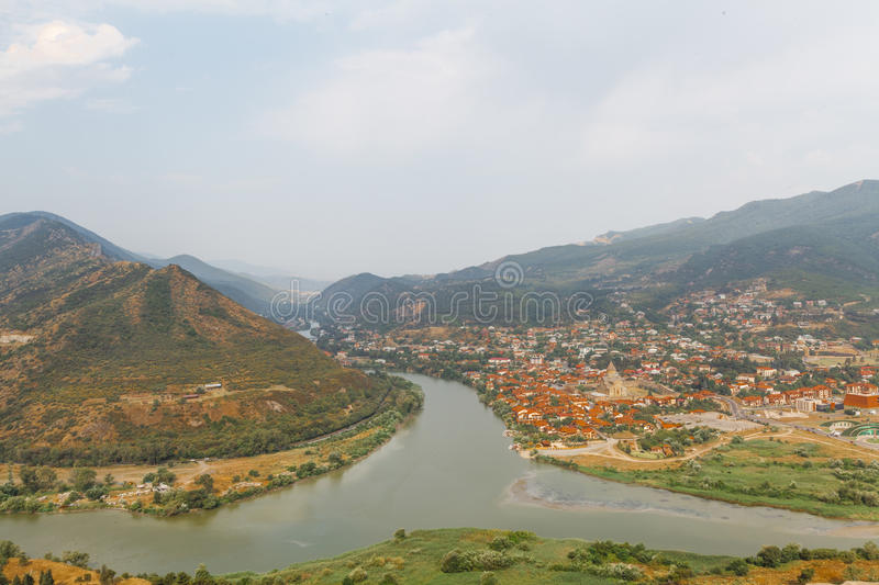View on Mtskheta, one of the oldest cities of Georgia, from Jvari Monastery. Confluence of the Mtkvari and Aragvi rivers with. Visible color difference. Cloudy stock images