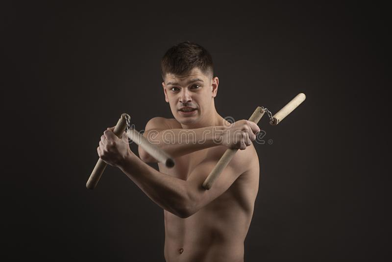 Studio shot of a muscled man in single combat weapon pose with nunchaku on a black background. View of a muscled man in single combat weapon pose with nunchaku stock photography