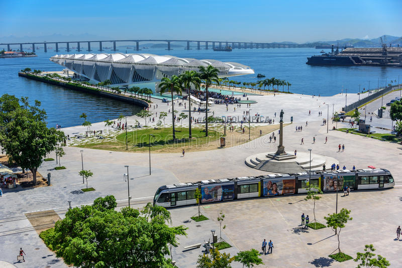 View of the Museum of Tomorrow, Light Rail passing Maua Square and Porto Maravilha with Rio-Niteroi Bridge on the background royalty free stock image