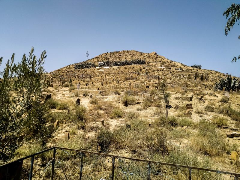 View of a Muslim graveyard typical of North African countries built on a hill.  Dirt graves. stock photo