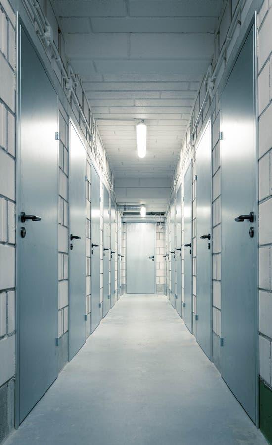 A long corridor in the basement with metal doors stock images