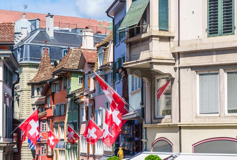 Narrow street with flags of switzerland in Zurich - Augustinergasse. View on narrow street with flags of switzerland in Zurich - Augustinergasse stock images