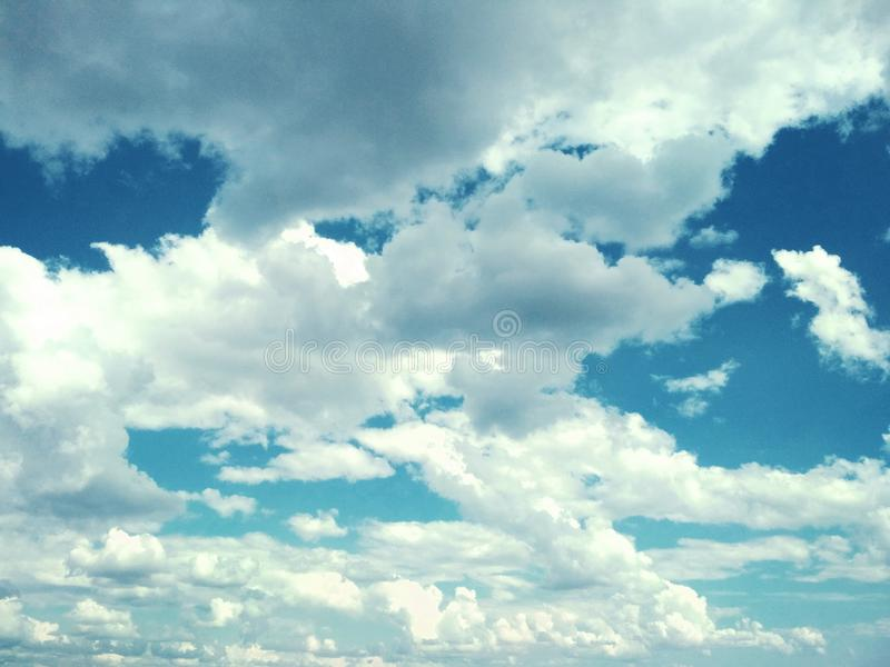 Cumulus clouds peacefully floating in the sky. View of a natural background, wool pack clouds that are peacefully floating in the sky stock images
