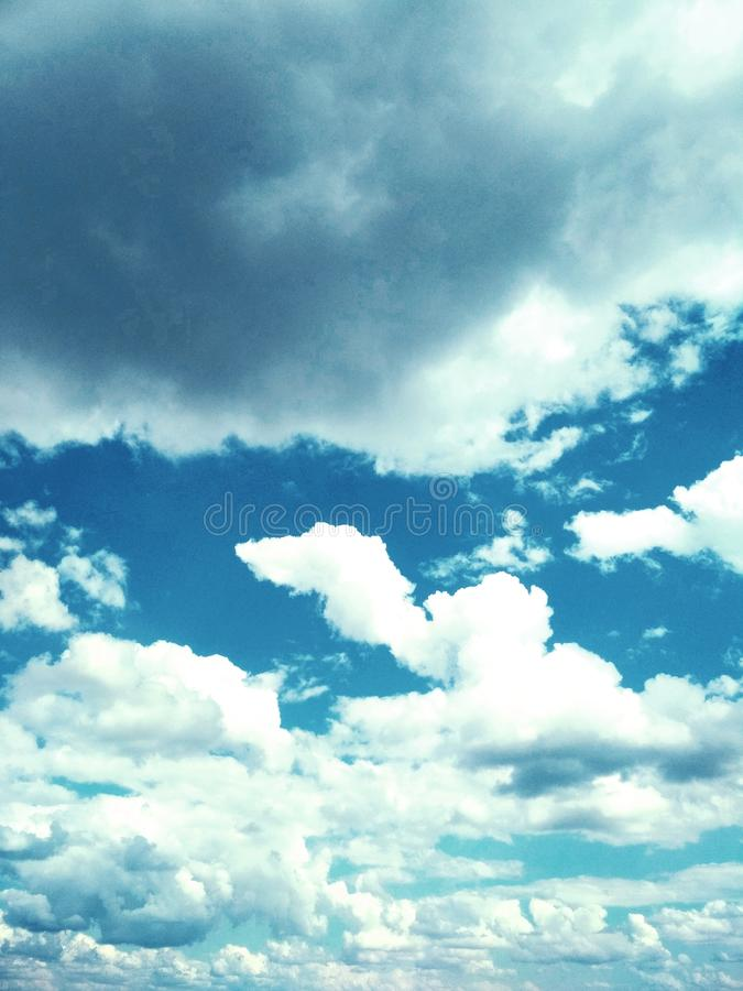 Cumulus clouds peacefully floating in the sky. View of a natural background, wool pack clouds that are peacefully floating in the sky royalty free stock image