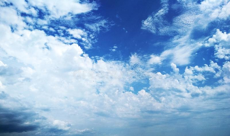 Cumulus clouds peacefully floating in the sky. View of a natural background, wool pack clouds that are peacefully floating in the sky royalty free stock photography