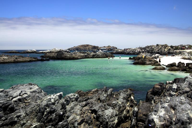 View on natural turquoise pool surrounded by jagged rocks with altostratus clouds in the horizon. Bahia Inglesa at pacific coast of Atacama desert, La Piscina royalty free stock image