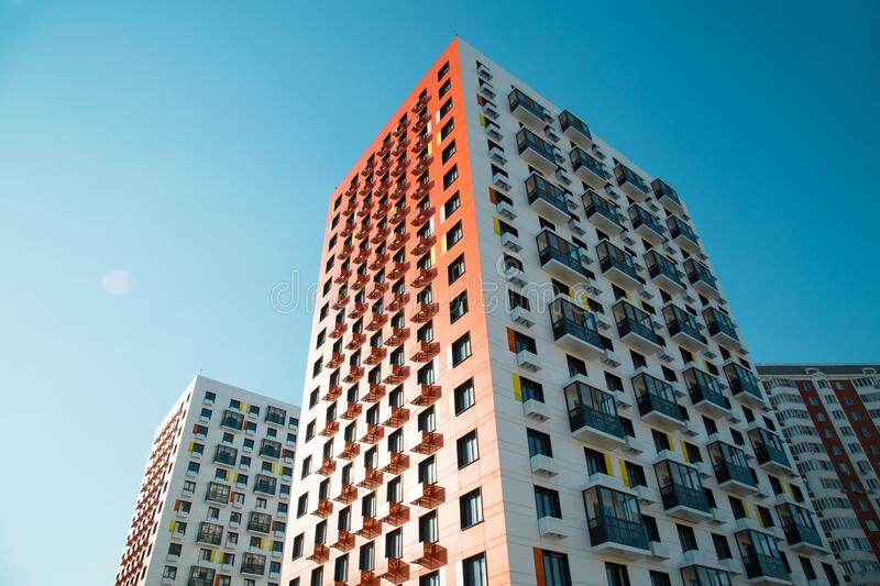 View of a new beautiful orange and white apartment buildings on a bright Sunny day in the rays of the setting sun, construction. Business Finance investment stock photo