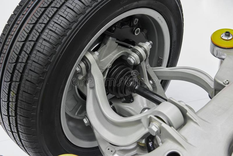 View on new car chassis suspension with wheel rim with tyre, driveshaft with dust cap, brake disc elements, arms with silentblocks stock photos