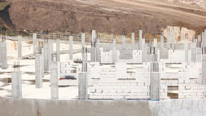 View on new construction site. Construction of unfinished cottage from white bricks. Developer project on field royalty free stock image
