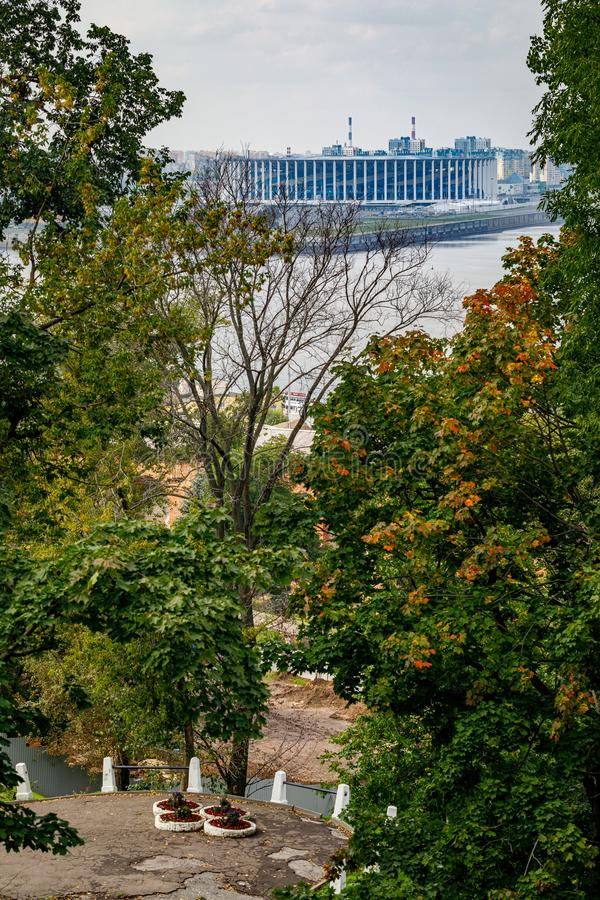 View of the new football stadium. Viewpoint in the historical part of Nizhny Novgorod. View of the famous futbol stadium. In Nizhny Novgorod through the trees stock images