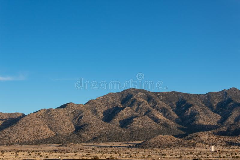 View of New Mexico plains and mountains, desert southwest winter, blue sky copy space. Horizontal aspect stock photography