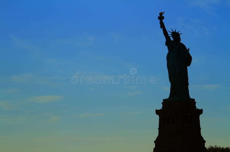 View of New York City, USA. Staue of Liberty silhouette at suns stock image