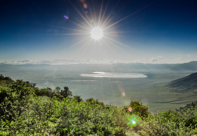 View of Ngorongoro Crater from the Rim. A view of the Ngorongoro Crater, with lake Magadi visbible in the distance infront of the clowds which cover the crater royalty free stock photo