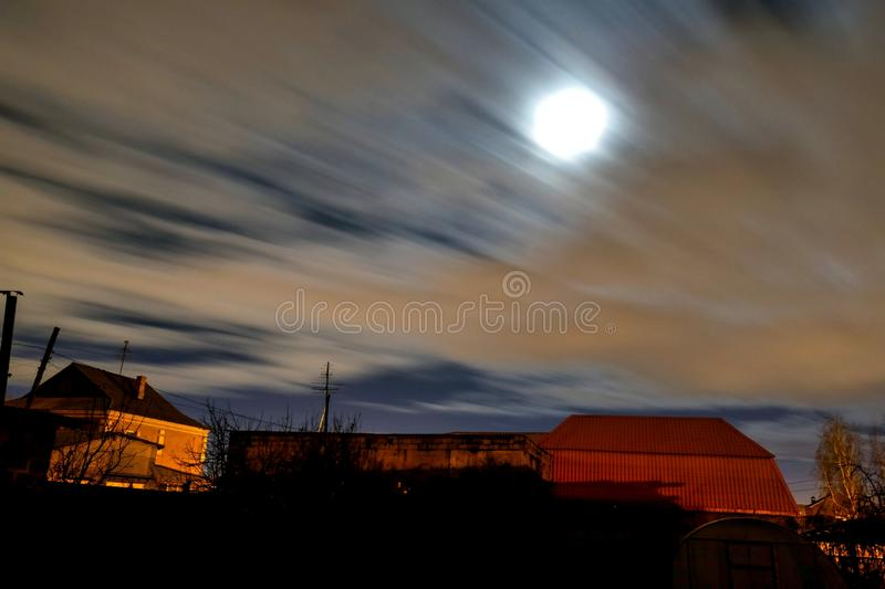 View of the night moon sky in windy cloudy weather. View of the night moon sky with fast-flying clouds in the suburbs, wind, fog stock images