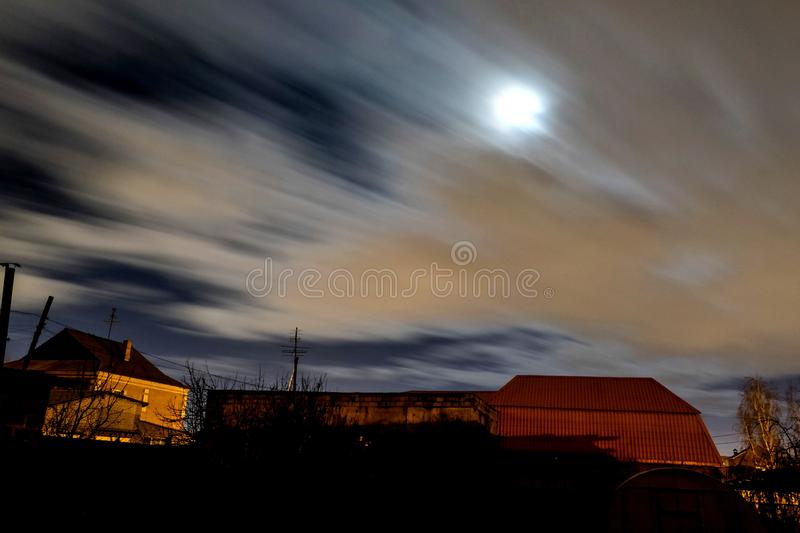 View of the night moon sky in windy cloudy weather. View of the night moon sky with fast-flying clouds in the suburbs, wind, fog royalty free stock photo