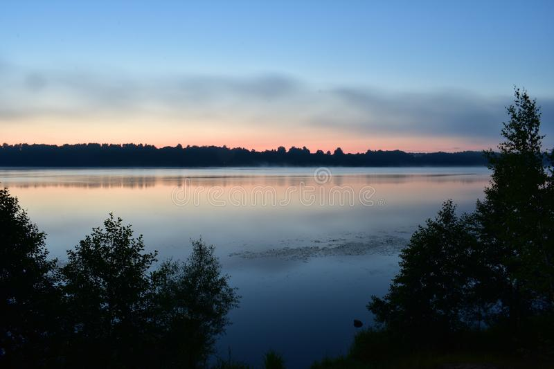 View of the night river with a water surface as a mirror reflected in the water forest and clouds stock photos