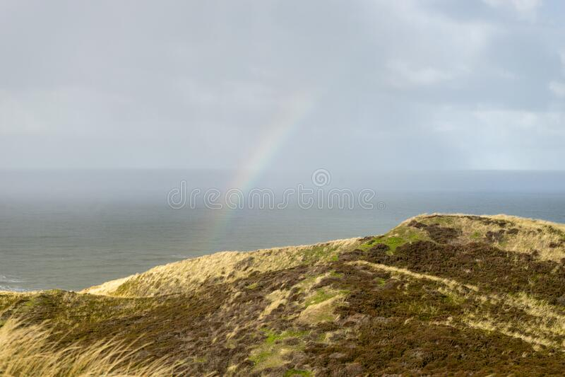 North Sea with rainbow and dunes royalty free stock photos