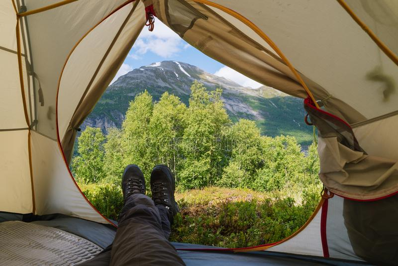 Guy is looking from the tent to the mountains stock images
