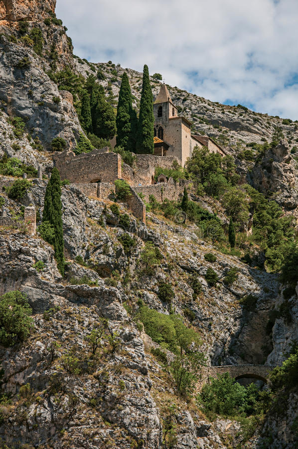 View of the Notre-Dame de Beauvoir church amidst cliffs and rock stairway, above the Moustiers-Sainte-Marie village. stock photos