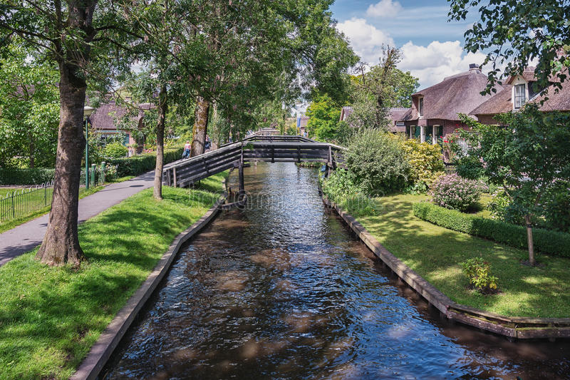 View of a number of wooden bridges across the canal. A view of a number of bridges across the canal in the Dutch town of Giethoorn stock images